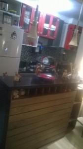 Cozinha ambientada acom armarios de caixotes com portas cristaleira e balcao americano com frente ripada